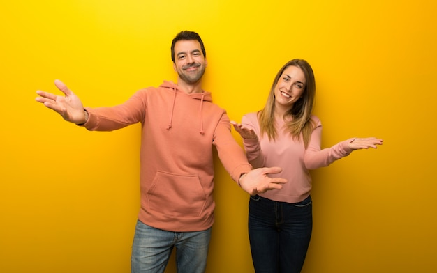 In valentine day group of two people on yellow background presenting and inviting to come with hand