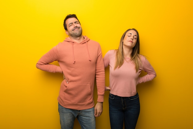 In valentine day group of two people on yellow background suffering from backache for having made an effort