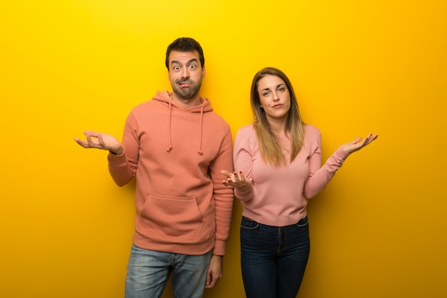 In valentine day group of two people on yellow background unhappy and frustrated with something because not understand something