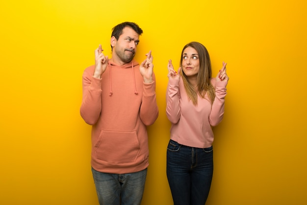 In valentine day group of two people on yellow background with fingers crossing and wishing the best
