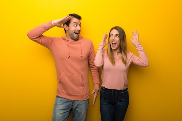 In valentine day group of two people on yellow background with surprise and shocked facial expression