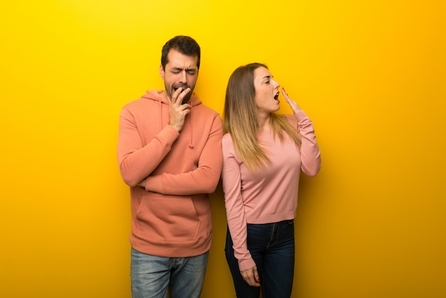 In valentine day group of two people on yellow background yawning and covering wide open mouth with hand