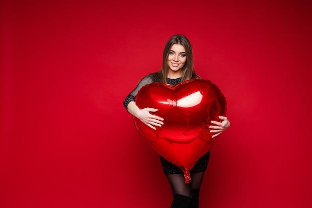 Праздник дня святого валентина, молодая девушка обнимает воздушный шар в форме сердца с пустым пространством для рекламы на красном
