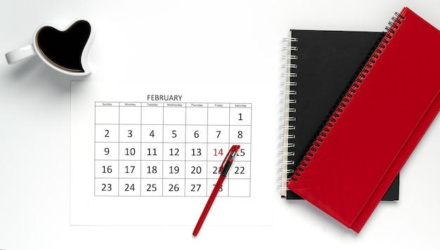 День святого валентина в офисе. февральский календарь с чашкой кофе в форме сердца и цветными блокнотами на столе