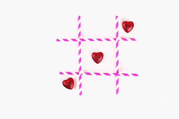 Valentine day layout. noughts and crosses pink straws and hearts on a white background. tic tac toe.