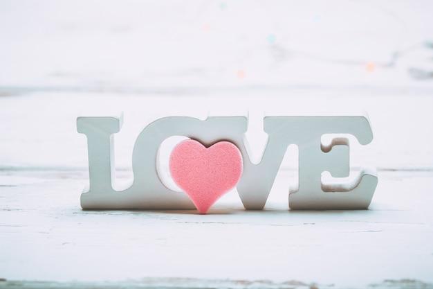 バレンタインデーの愛の概念。白い木製の背景にピンクのハートと木製の白いレタリングの愛