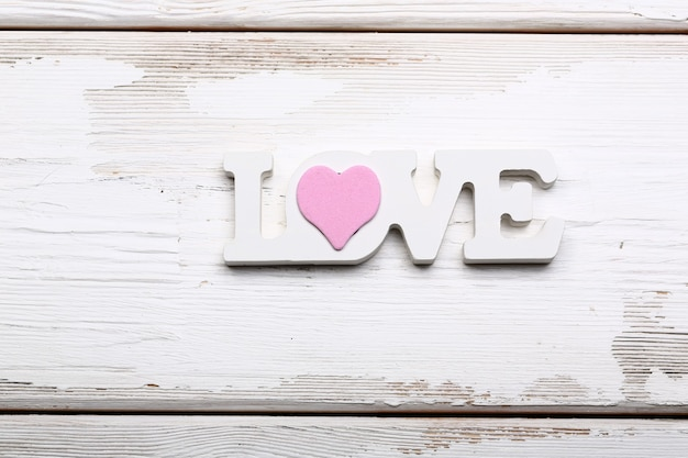 Valentine day love concept. wooden white lettering love with pink heart on white wooden background