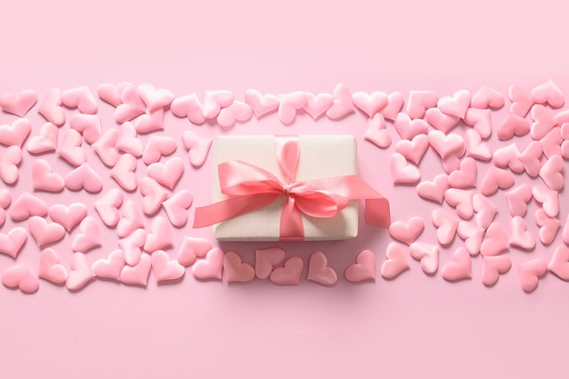 Valentine day or newborn girly gift and hearts on pink background. romantic greeting card with copy space.