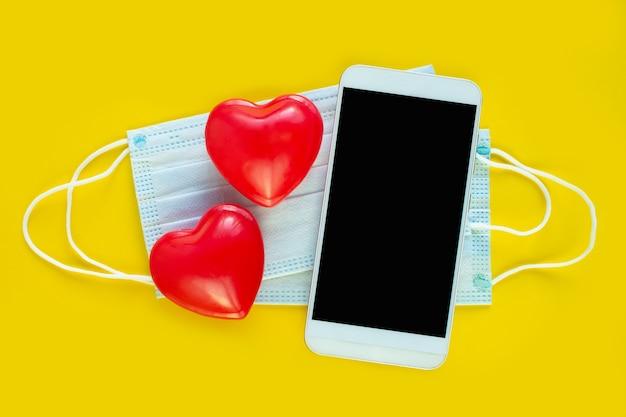 バレンタインデーオンラインおめでとう、オンラインショッピング。スマートフォン、医療用マスク、赤いハート。