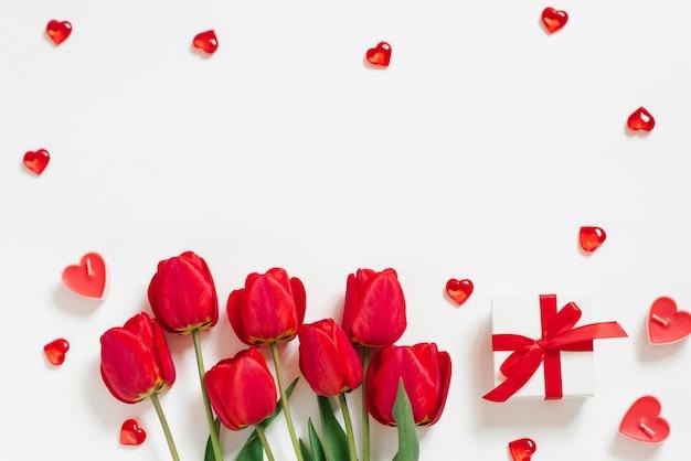 Валентина романтический фон. красные тюльпаны, подарок с бантом и свечными сердечками на белом фоне с копировальным пространством. плоская планировка