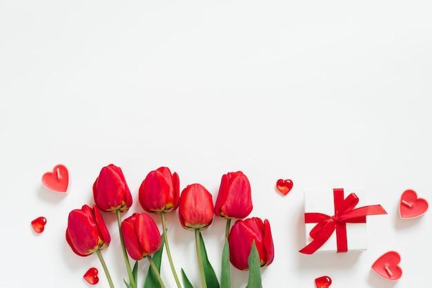 バレンタインデーのロマンチックな背景。赤いチューリップ、リボン付きギフト、キャンドルハート
