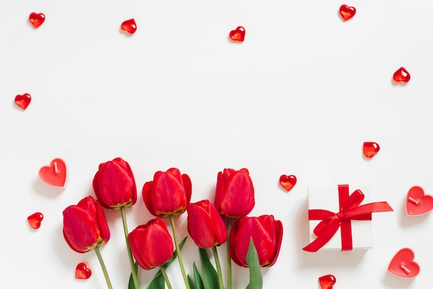 Valentine day romantic background. red tulips, a gift with a bow, and candle hearts on a white background with copying space. flat lay