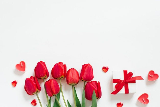 Valentine day romantic background. red tulips, a gift with a bow, and candle hearts