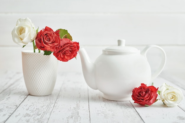 Valentine day romantic breakfast with red roses and teapot. happy valentine's day greeting card.