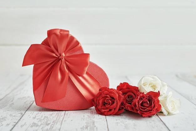 Романтическое украшение дня святого валентина с красными розами и подарочной коробкой. с днем святого валентина поздравительная открытка.