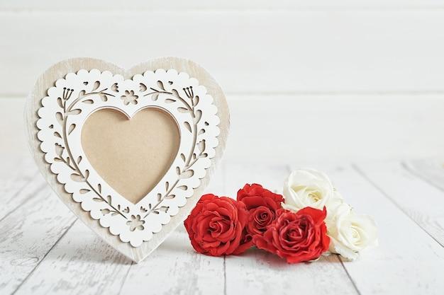 赤いバラの花とフレームのバレンタインの日ロマンチックな装飾。幸せなバレンタインデーのグリーティングカード。