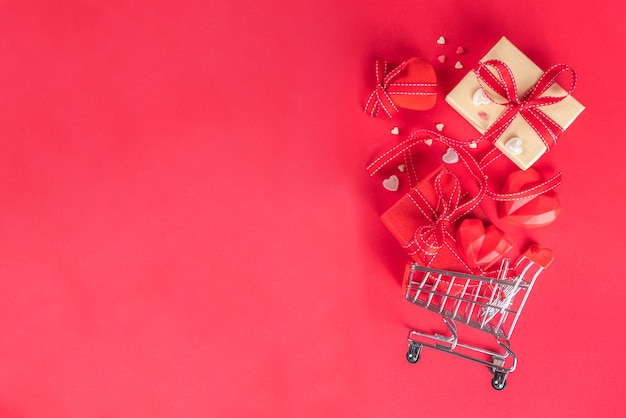 Valentine day sale, still life composition with festive gifts box, red heart and shopping cart