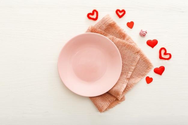 Сервировка стола в день святого валентина. сервировка пустая розовая тарелка с копией пространства сердца.