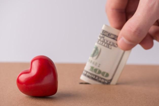 バレンタインデーの結婚式の利益の支払い。紙幣を穴に入れている男性の男性の手のトリミングされたクローズアップ写真