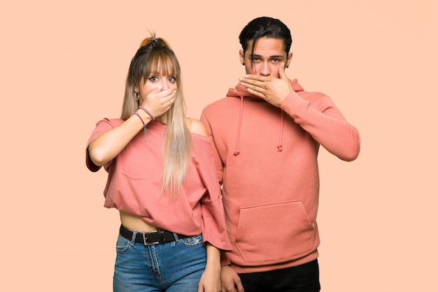 In valentine day young couple covering mouth with hands for saying something inappropriate over pink background