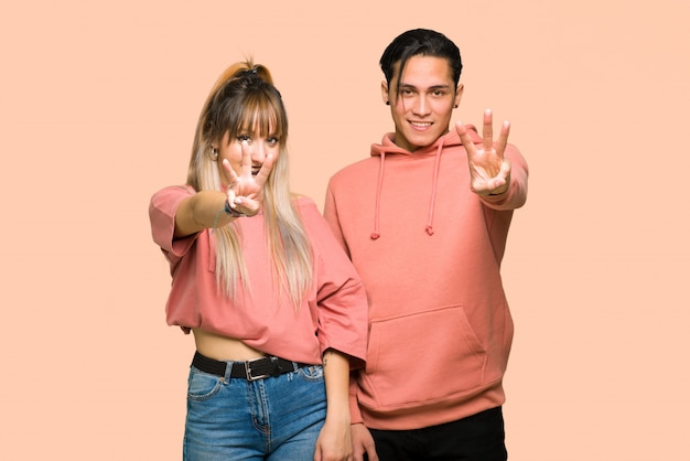 In valentine day young couple happy and counting three with fingers over pink background