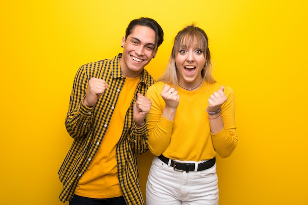 In valentine day young couple over vibrant yellow background celebrating a victory in winner position