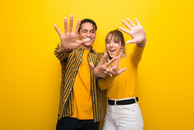 In valentine day young couple over vibrant yellow background counting eight with fingers