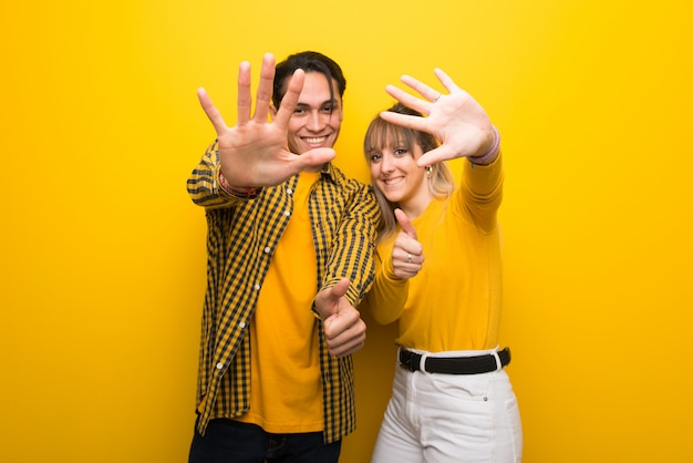 In valentine day young couple over vibrant yellow background counting six with fingers