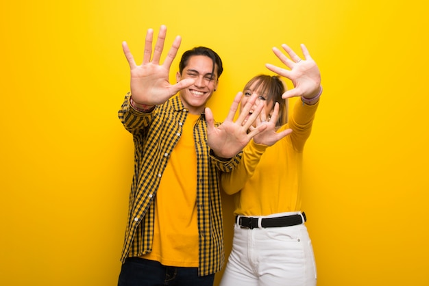 In valentine day young couple over vibrant yellow background counting ten with fingers
