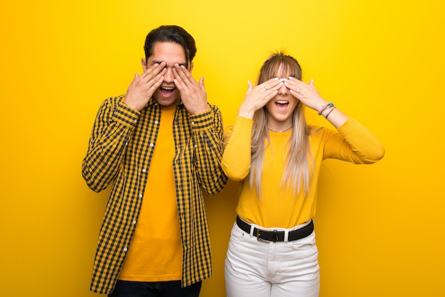 In valentine day young couple over vibrant yellow background covering eyes by hands. surprised to see what is ahead