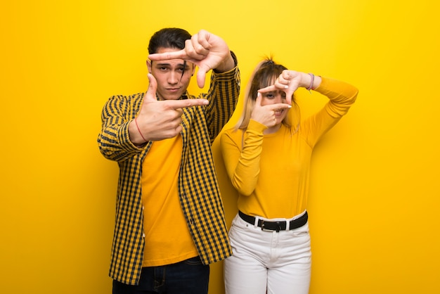 In valentine day young couple over vibrant yellow background focusing face. framing symbol