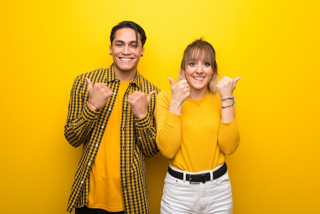 In valentine day young couple over vibrant yellow background giving a thumbs up gesture with both hands and smiling