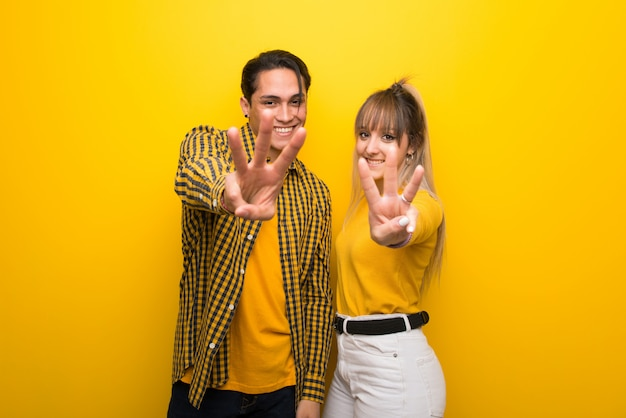 In valentine day young couple over vibrant yellow background happy and counting three with fingers