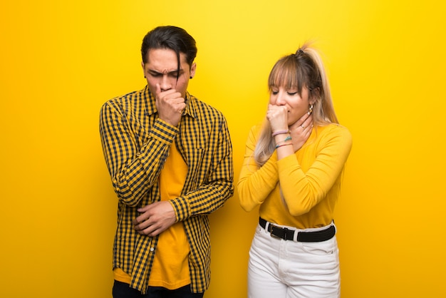 In valentine day young couple over vibrant yellow background is suffering with cough and feeling bad