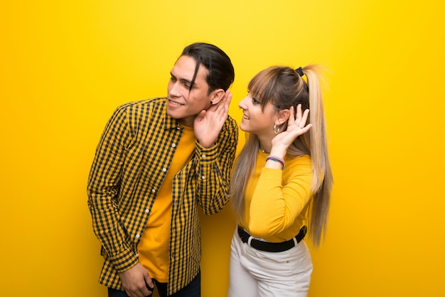 In valentine day young couple over vibrant yellow background listening to something by putting hand on the ear