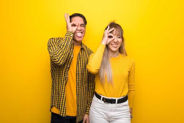 In valentine day young couple over vibrant yellow background makes funny and crazy face emotion
