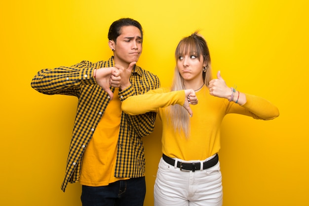 In valentine day young couple over vibrant yellow background making good-bad sign. undecided between yes or not