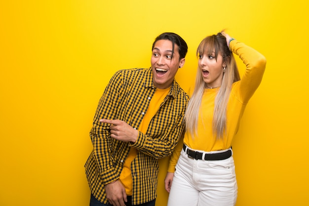 In valentine day young couple over vibrant yellow background pointing finger to the side and presenting a product