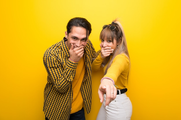 In valentine day young couple over vibrant yellow background pointing with finger at someone and laughing