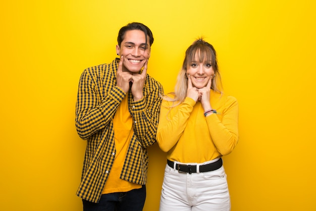 In valentine day young couple over vibrant yellow background smiling with a happy and pleasant expression