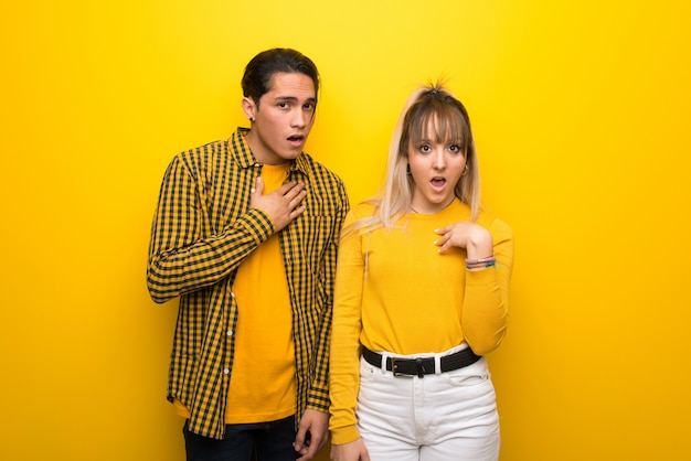 In valentine day young couple over vibrant yellow background surprised and shocked while looking right