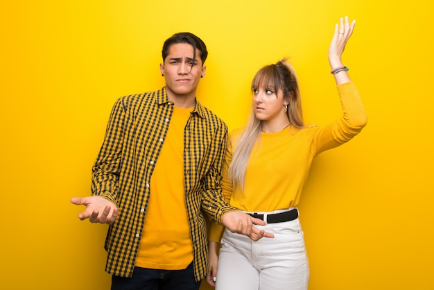 In valentine day young couple over vibrant yellow background unhappy and frustrated with something because not understand something