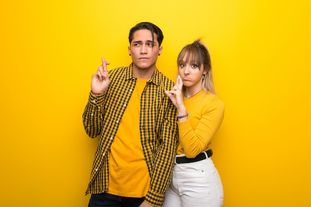 In valentine day young couple over vibrant yellow background with fingers crossing and wishing the best