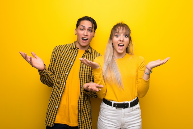 In valentine day young couple over vibrant yellow background with surprise and shocked facial expression