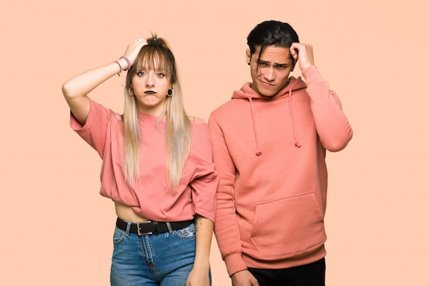 In valentine day young couple with an expression of frustration and not understanding over pink background
