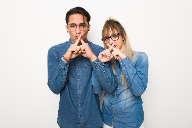 In valentine day young couple with glasses showing a sign of silence gesture