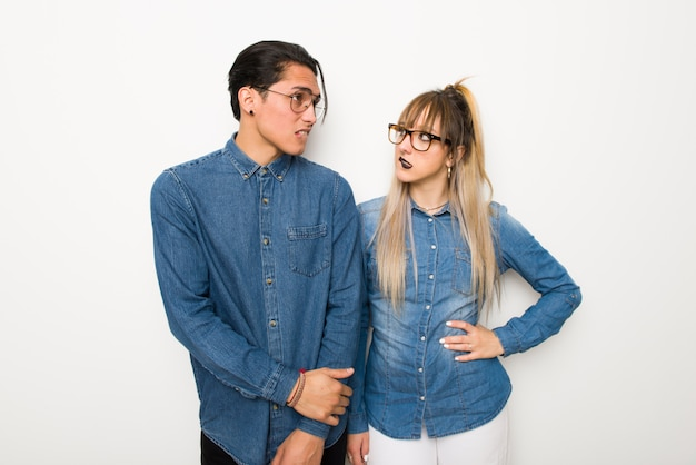 In valentine day young couple with glasses with confuse face expression while bites lip