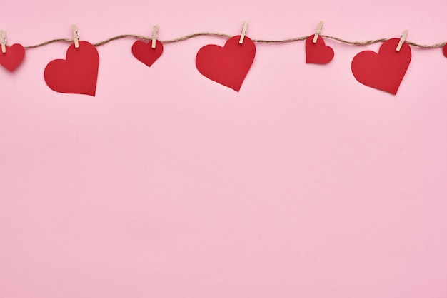 День святого валентина красные бумажные сердечки, висящие на веревке для белья