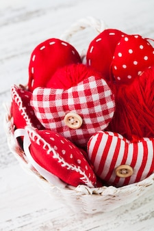 Валентина украшения: текстильные красные сердечки в белой корзине на обшарпанном столе