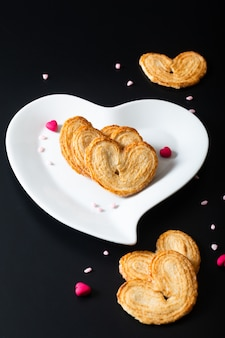 Valentine dessert food concept puff pastry hearts in white ceramic heart shape on black